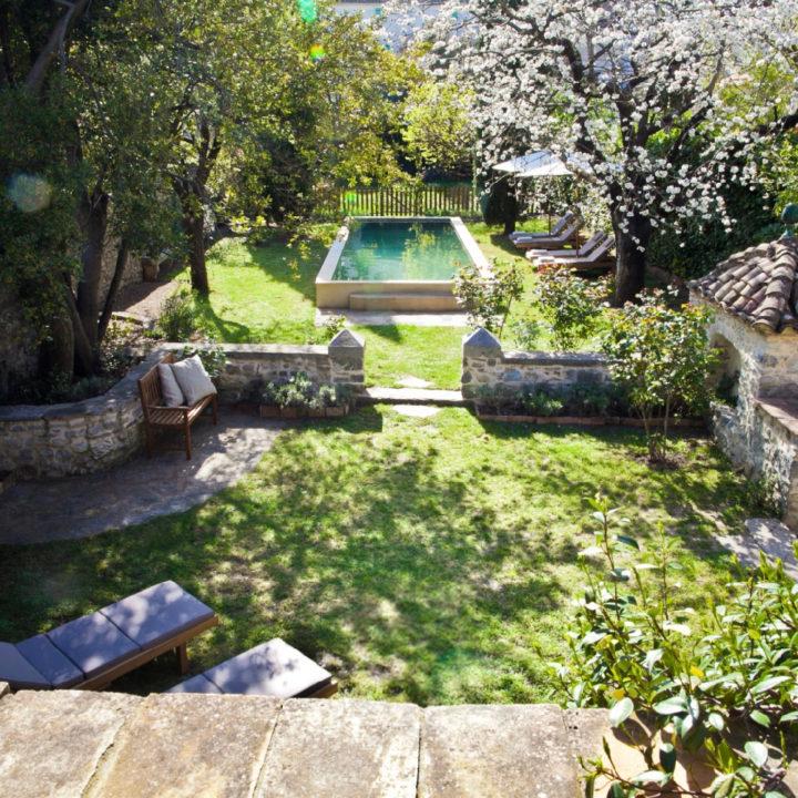 Ommuurde tuin met een zwembad, veel gras en diverse zitjes