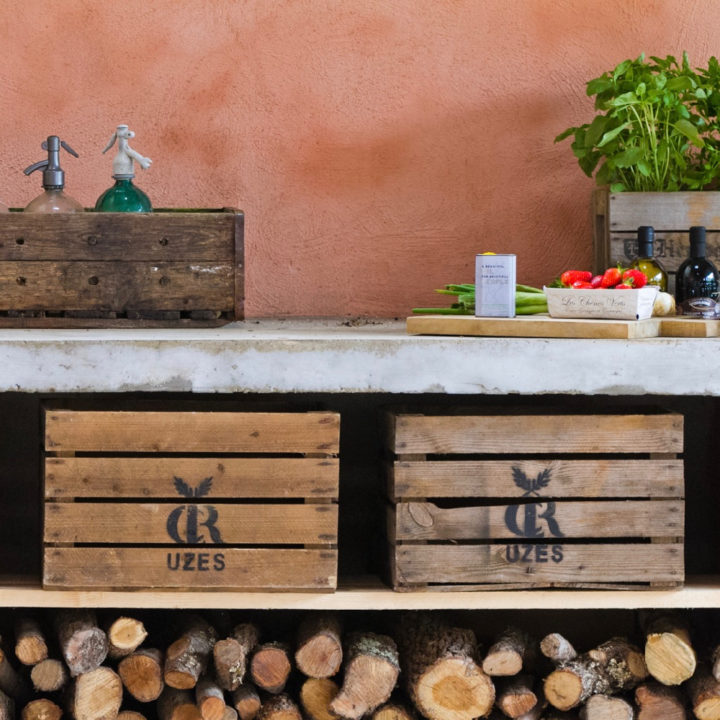 Aardekleurige muur met betonnen aanrechtblad met eronder haardhout, twee kisten en groente