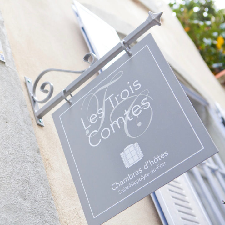 Uithangbordje aan de gevel met de naam Les Trois Comtes