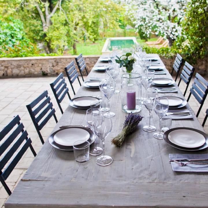 Lange gedekte tafel op de veranda, met zicht op de tuin met zwembad
