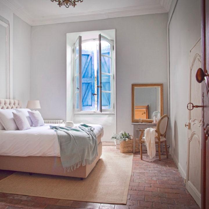 Een luxe kamer van Les Trois Comtes met een tweepersoonsbed en groot raam