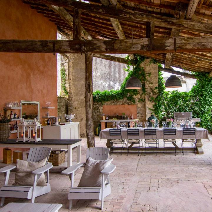 Een prachtige veranda met loungehoek en lange tafel met stoelen