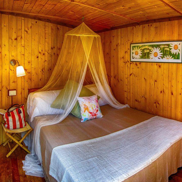 Tweepersoons opgemaakt bed met klamboe