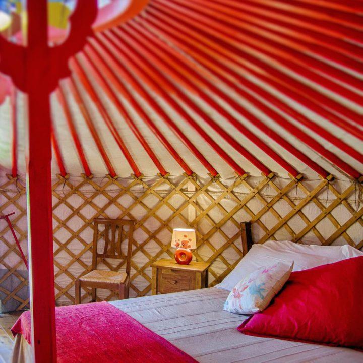 Een van de yurts van La Prugnola, met rood hout en een opgemaakt bed