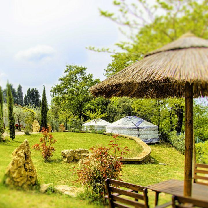 Twee Mongoolse yurts in een tuin met veel groen