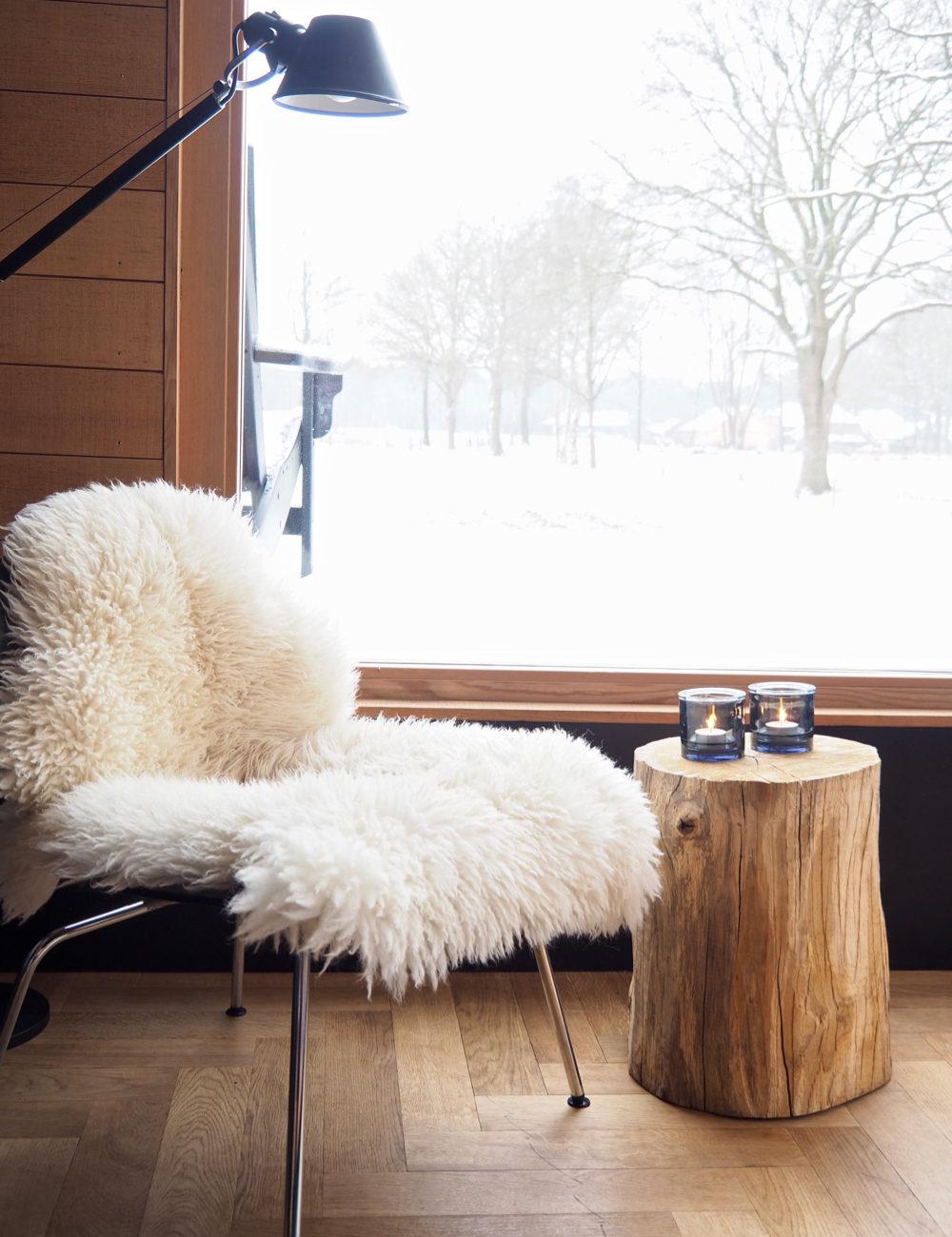 Een stoel met een witte schapenvacht voor een groot raam met uitzicht op een sneeuwlandschap