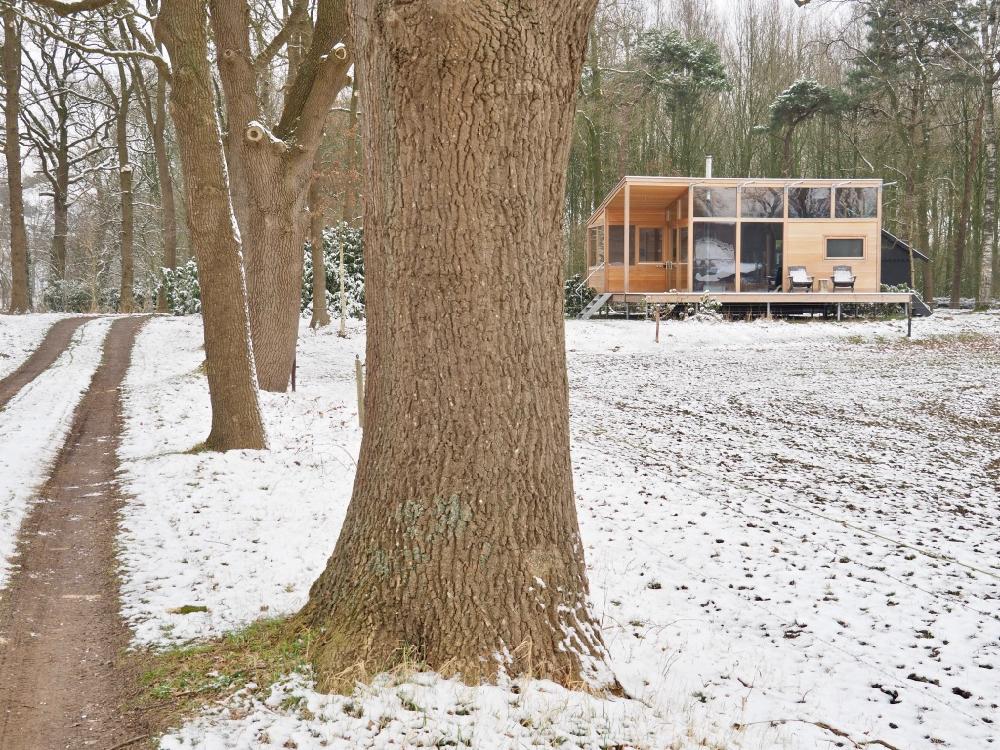Houten vakantiehuis aan het einde van een oprijlaan, bedekt met een laagje sneeuw