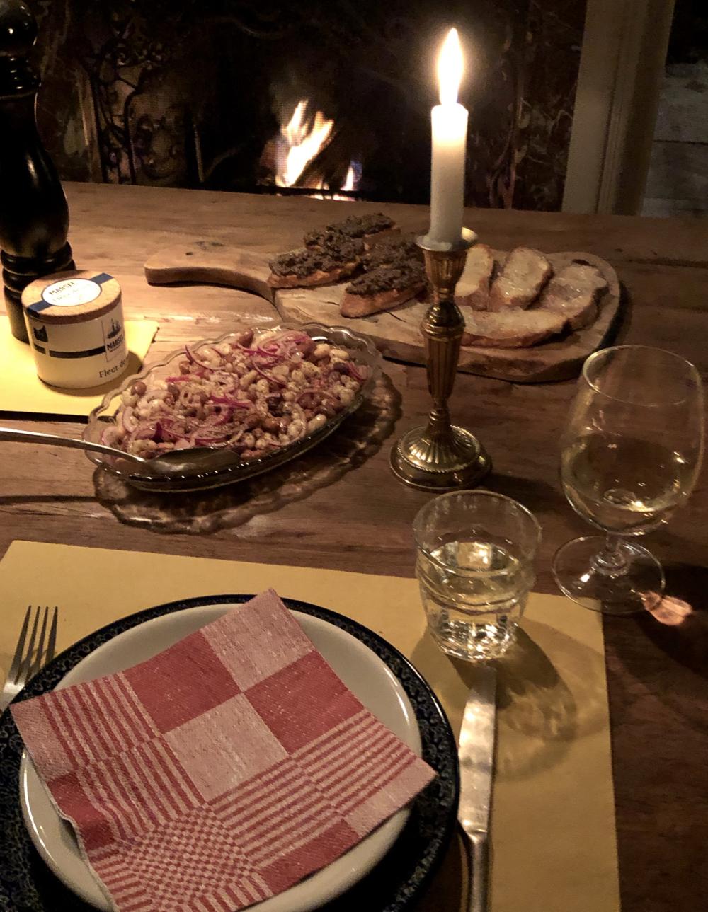 Gedekte tafel voor een haardvuur, met brandende kaars, en amuses