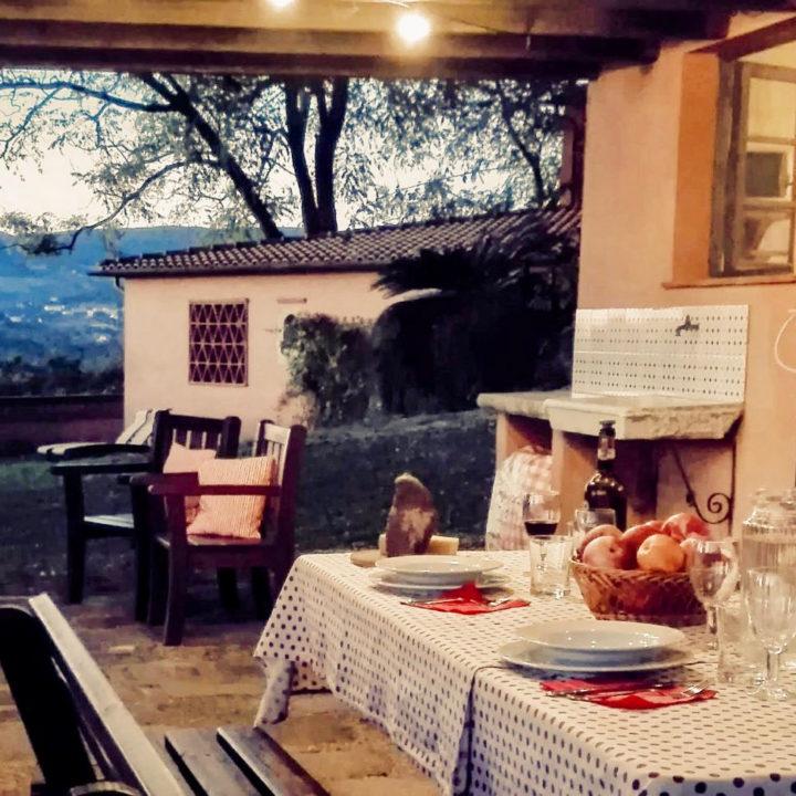 Gedekte tafel onder een overkapping, in de avondschemering