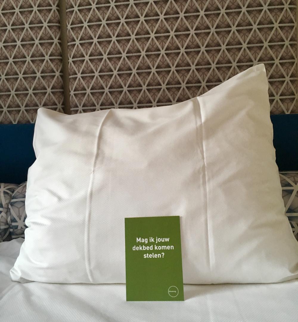 Een wit kussen op een wit dekbed met een groen kaartje met de tekst: mag ik je deken pakken
