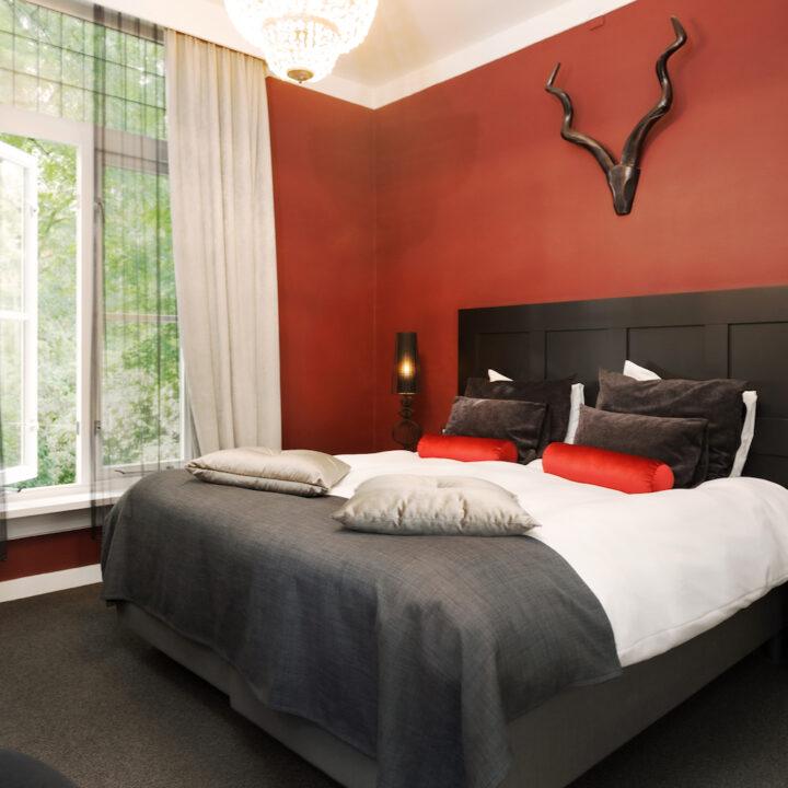 Hotelkamer met roodbruine wand met een gewei
