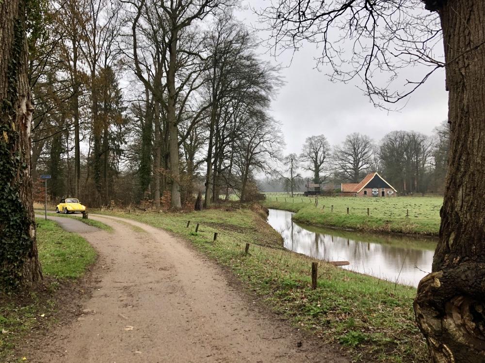 Een gele Volkswagen Kever op een landweg bij Watermolen Noordmolen op Landgoed Twickel