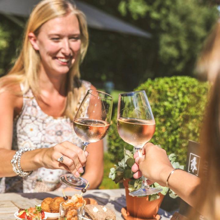 Dames proosten met wijnglazen, op terras in de zon