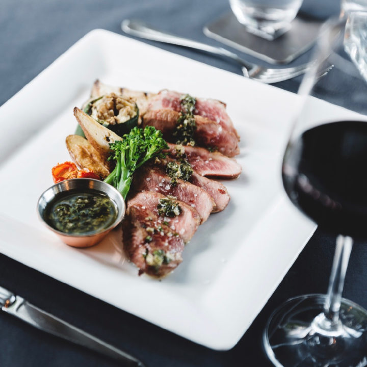 Wit dinerbord met vlees en rood glas wijn