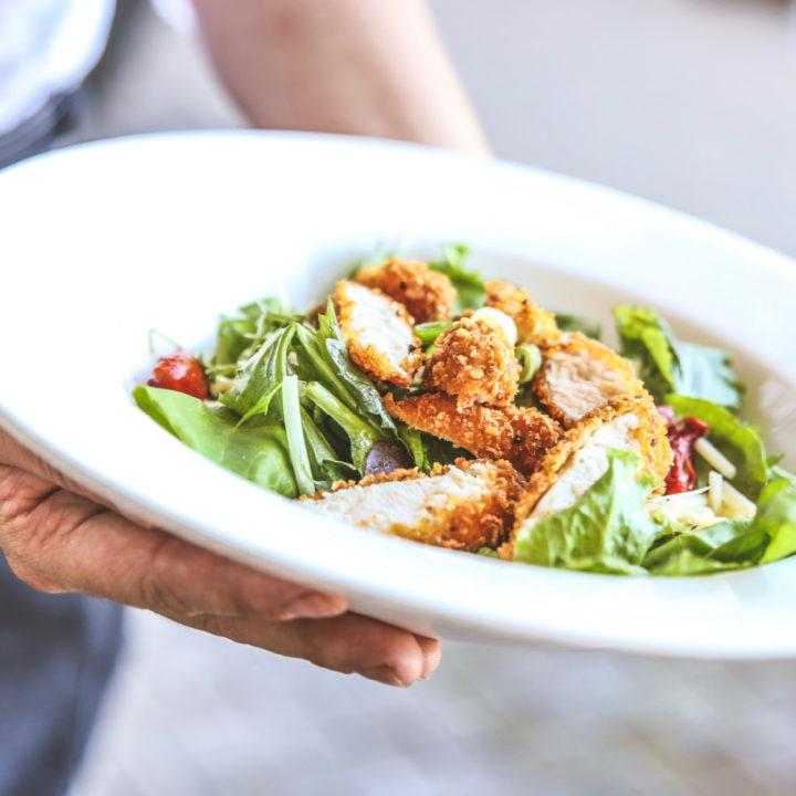 Handen met een wit bord salade