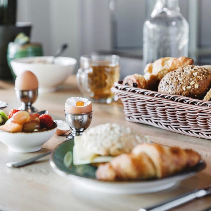 Ontbijttafel met gekookte eitjes, broodjes en croissants