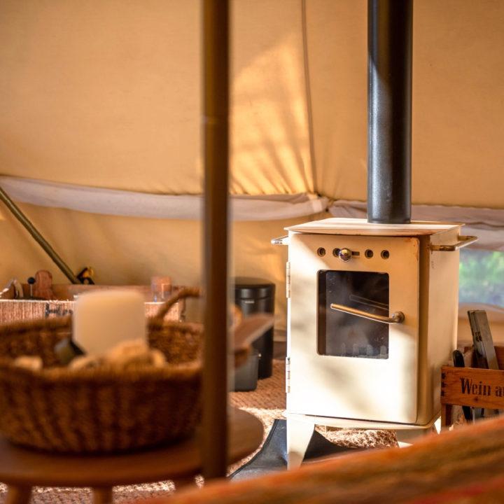 De Bell tent heeft een witte houtkachel
