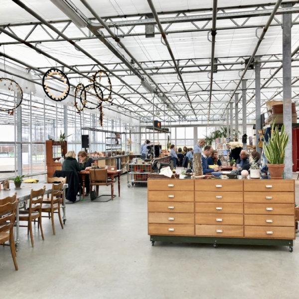 Kas met restaurant, grote ladenkast en houten stoelen bij de tafels