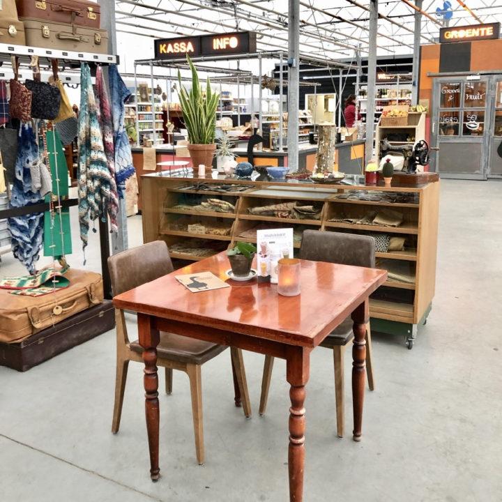 Tafeltje met stoelen, vitrinekast en rek met kleding in een kas