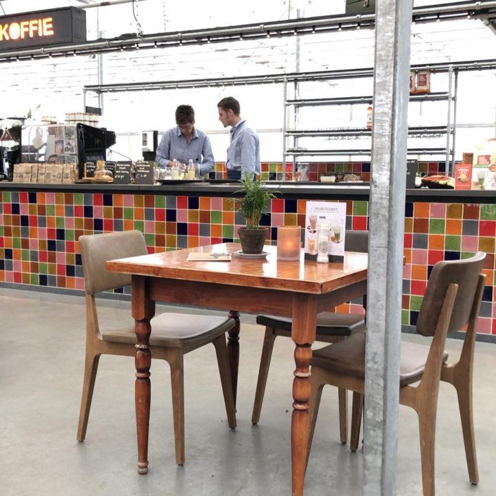 Grote bar met gekleurde tegels en tafeltje met stoelen