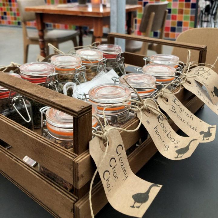 Potjes met thee en labels van karton eraan met de naam van de thee