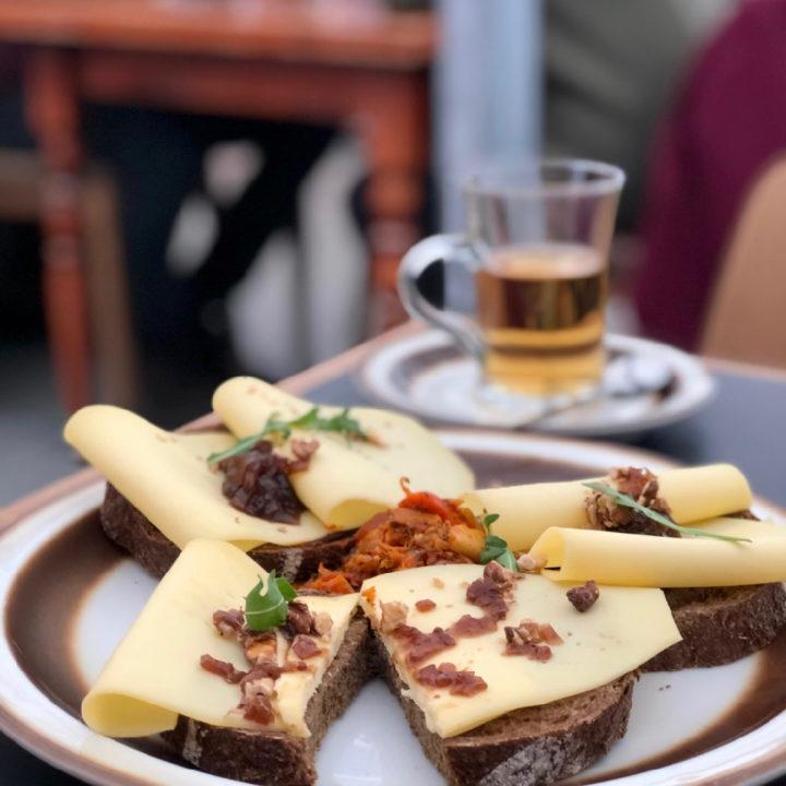 Bord met bruine boterham met kaas en kopje thee