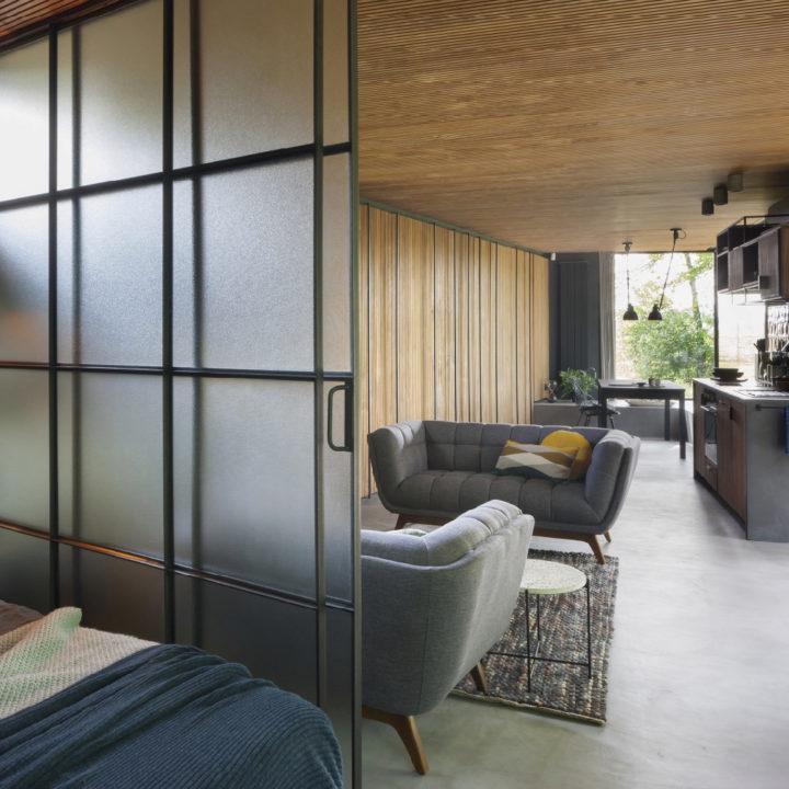 Stalen schuif ramen met doorkijk naar woonkamer, keuken en eethoek