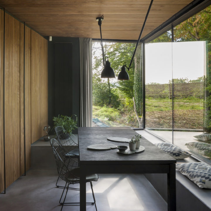 Strakke zwarte eettafel met stalen frame stoeltjes en enorme ramen met uitzicht op groen