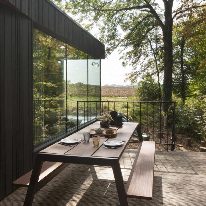 Terras in de zon met moderne gedekte picknicktafel
