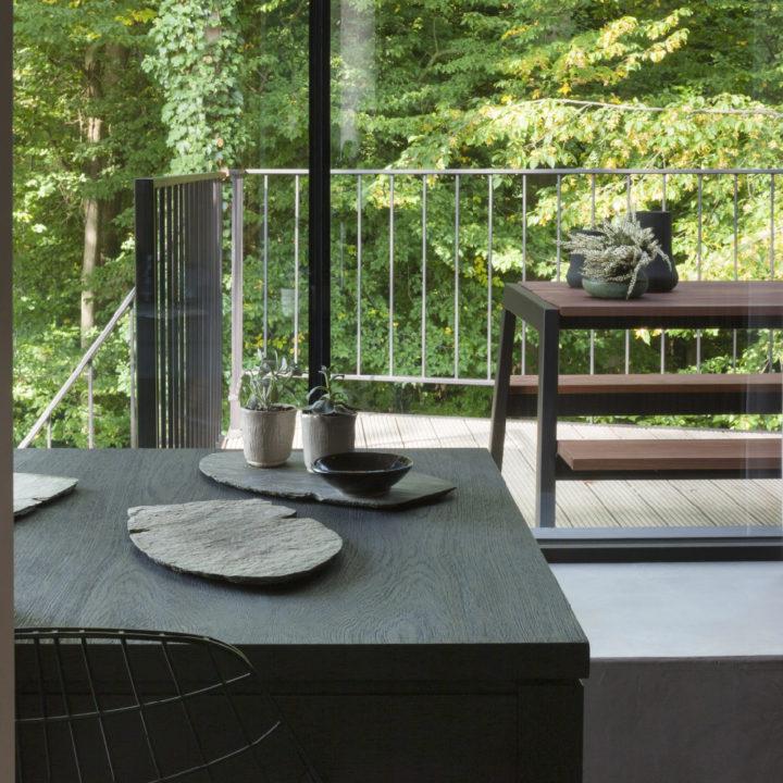 Zicht over de eettafel naar buiten, waar een moderne picknicktafel staat.