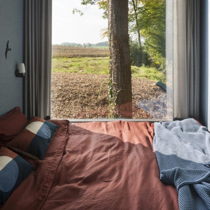 Tweepersoons bed met groot raam en zicht over de akkers vanuit Loof Cabin