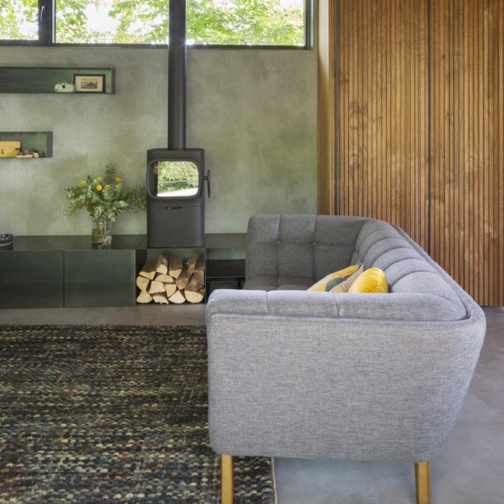 Zithoek met grijze bank, houtkachel en vaas met bloemen