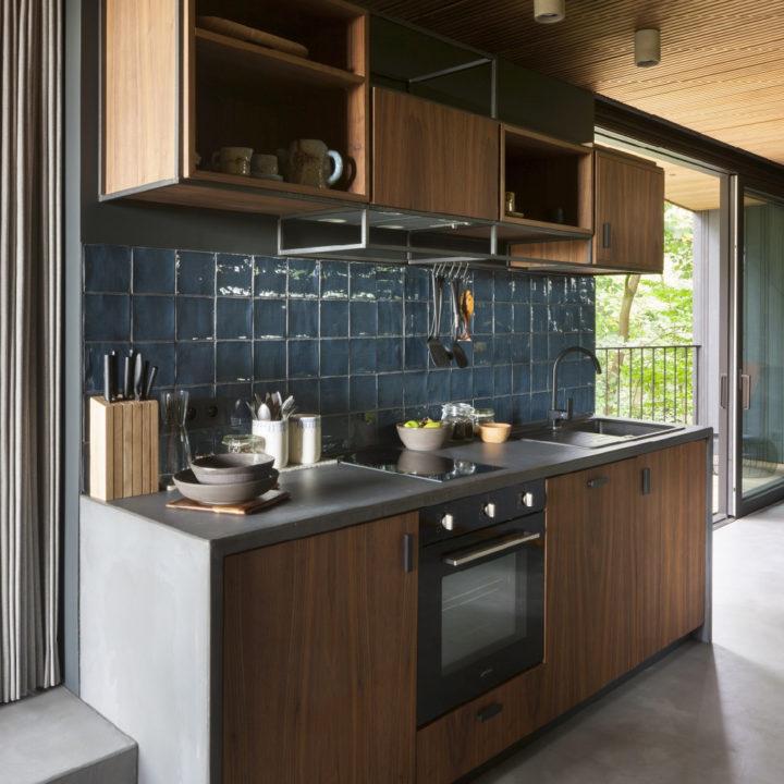 Moderne houten keuken met betonnen aanrechtblad en blauwe tegels