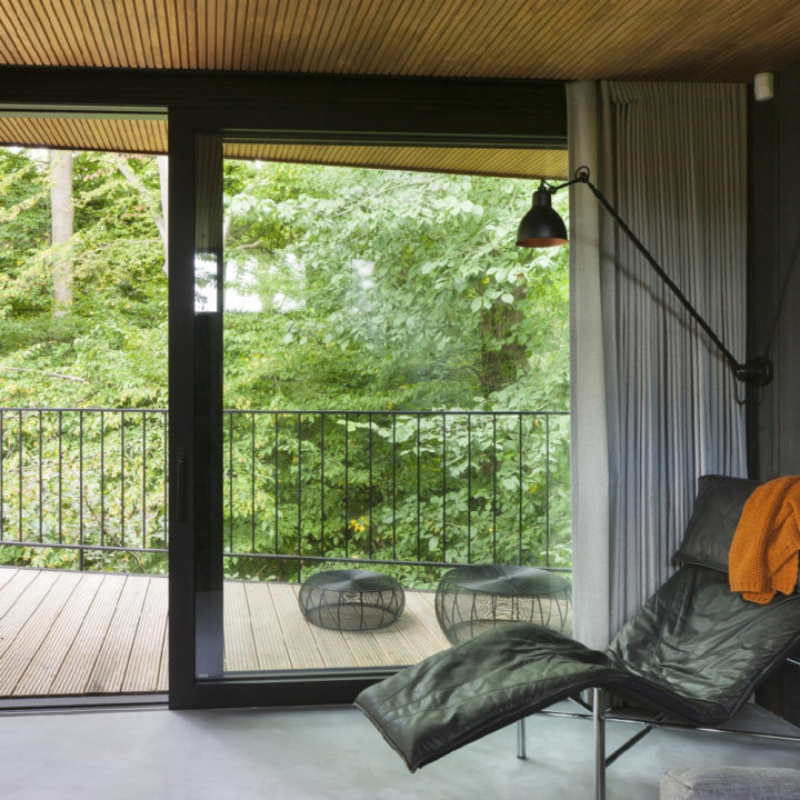 Zwarte leren ligstoel met schuifdeur naar balkon