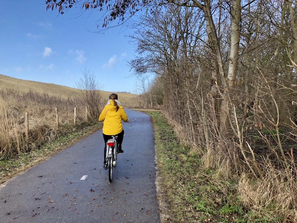 Een meisje met een gele regenjas op de fiets