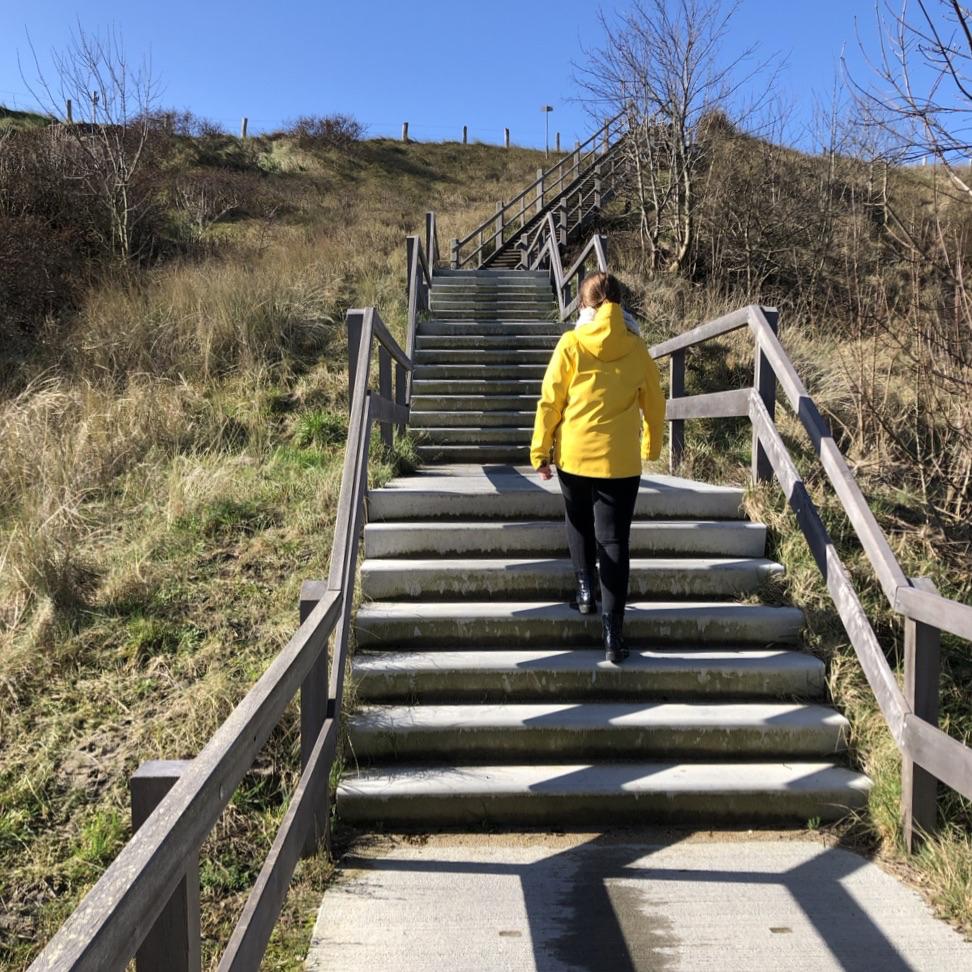 Een lange houten trap de duinen op, met daarop een meisje met een gele regenjas