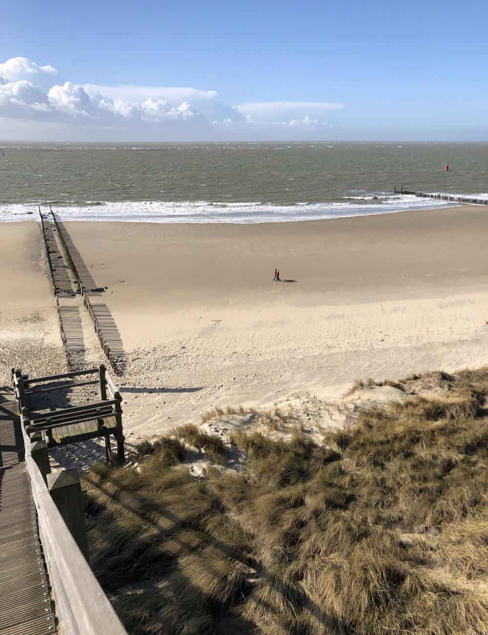 Trappen naar zee en stormbrekers op het strand