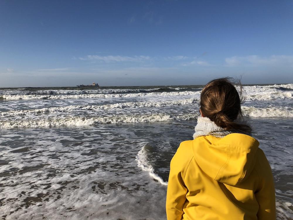 Een meisje met een gele regenjas aan de rand van een woeste zee