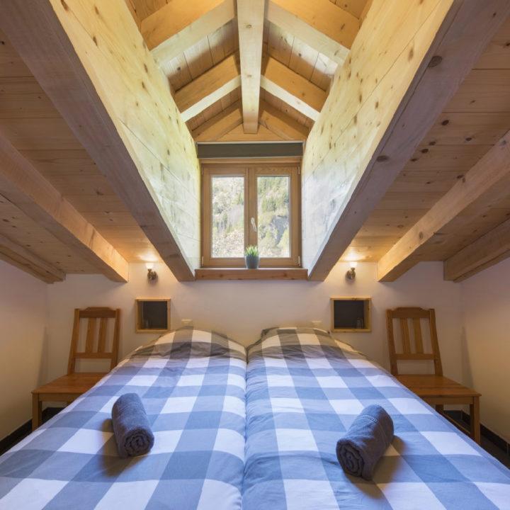 Tweepersoons bed met geblokt dekbed onder balkenplafond