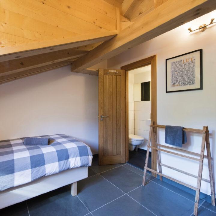 Een van de slaapkamers in het chalet, met een eenpersoons bed en houten wasrek als kledingrek.