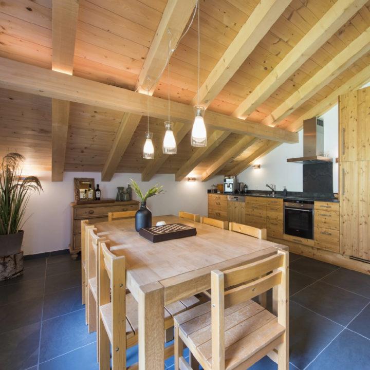 De keuken onder het schuine dak van het appartement op de 2e verdieping. Veel hout, houten eettafel, houten dak, houten keuken