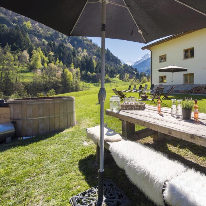 Picknicktafel met parasol en jacuzzi in de tuin van Zwitsers vakantiehuis