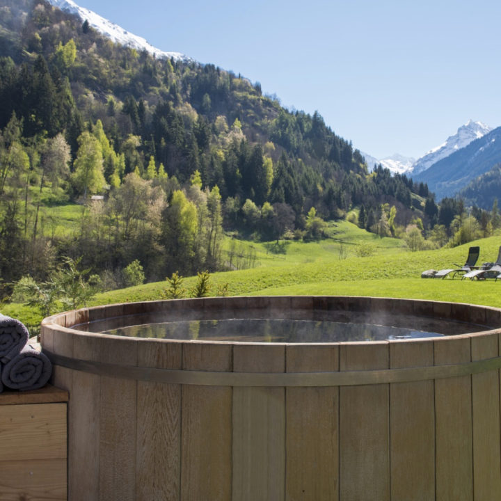 Close up van jacuzzi in de tuin van vakantiehuis, zicht op de bergen