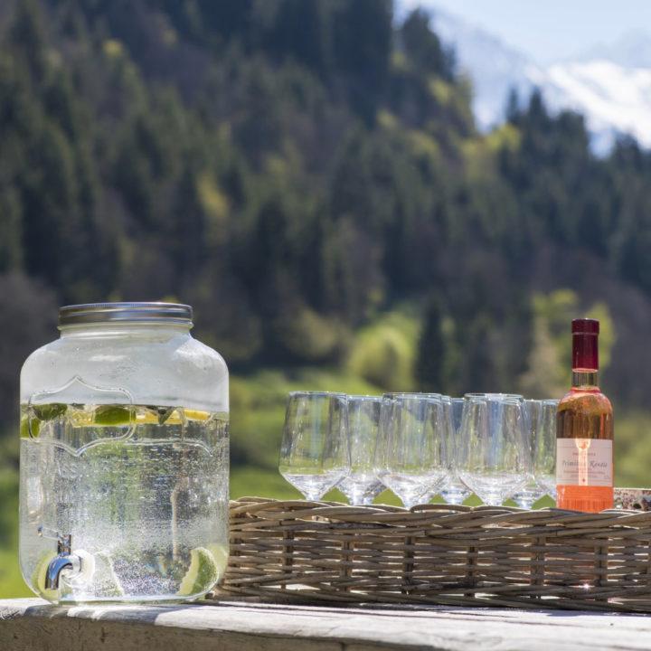 Tafel met wijnglazen, een fles rosé en een karaf met water in de zon