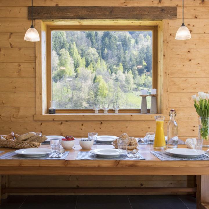 Gedekte tafel met ontbijt voor een groot raam met zicht op de bergen
