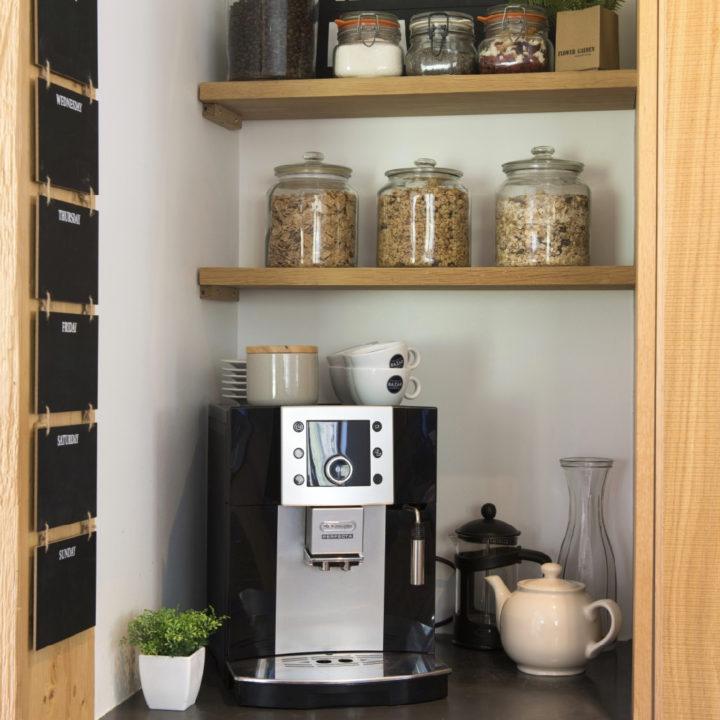 Koffiezetapparaat en planken met kopjes