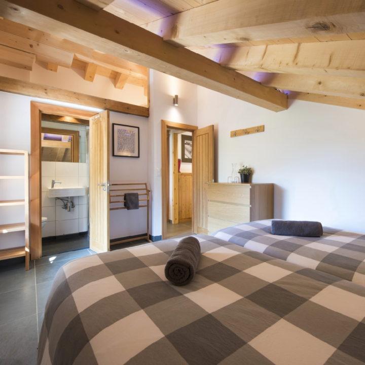 Opgemaakte bedden met geblokt dekbek, open deur naar de badkamer en open deur naar de gang