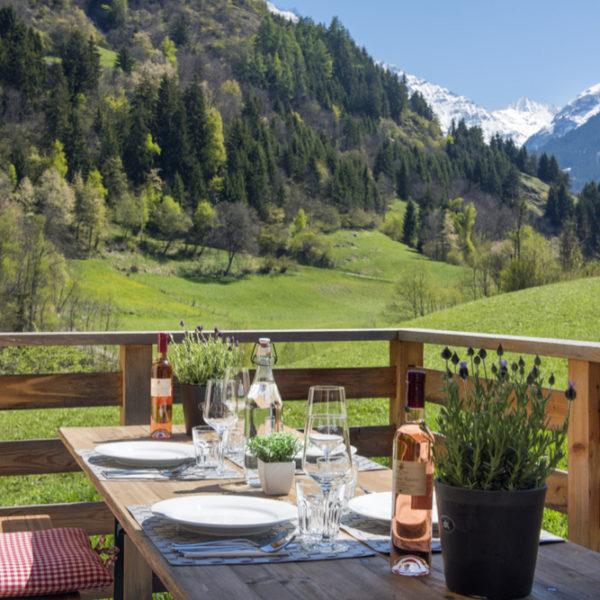 Gedekte tafel op terras met zicht op besneeuwde bergtoppen