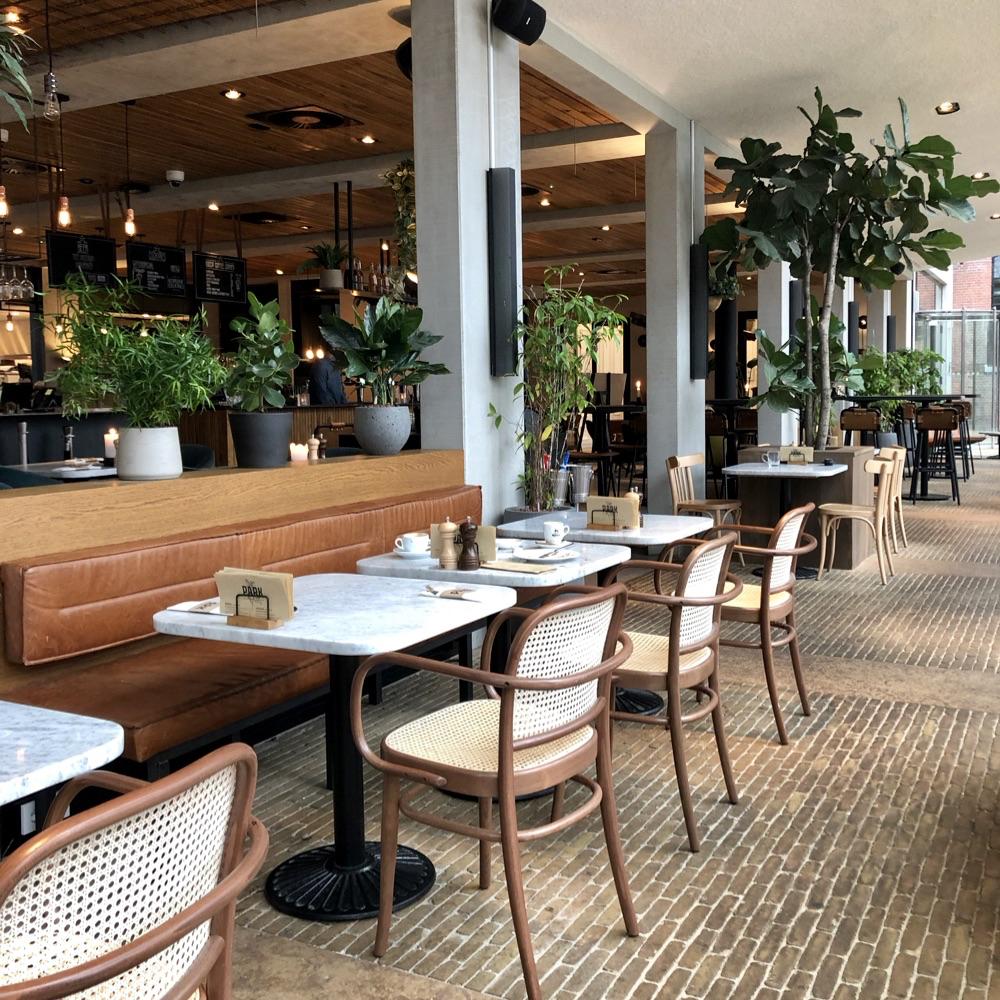 Een rij tafels met stoeltjes aan een zijde en een lange bruine leren bank aan de andere zijde. Planten als afscheiding.