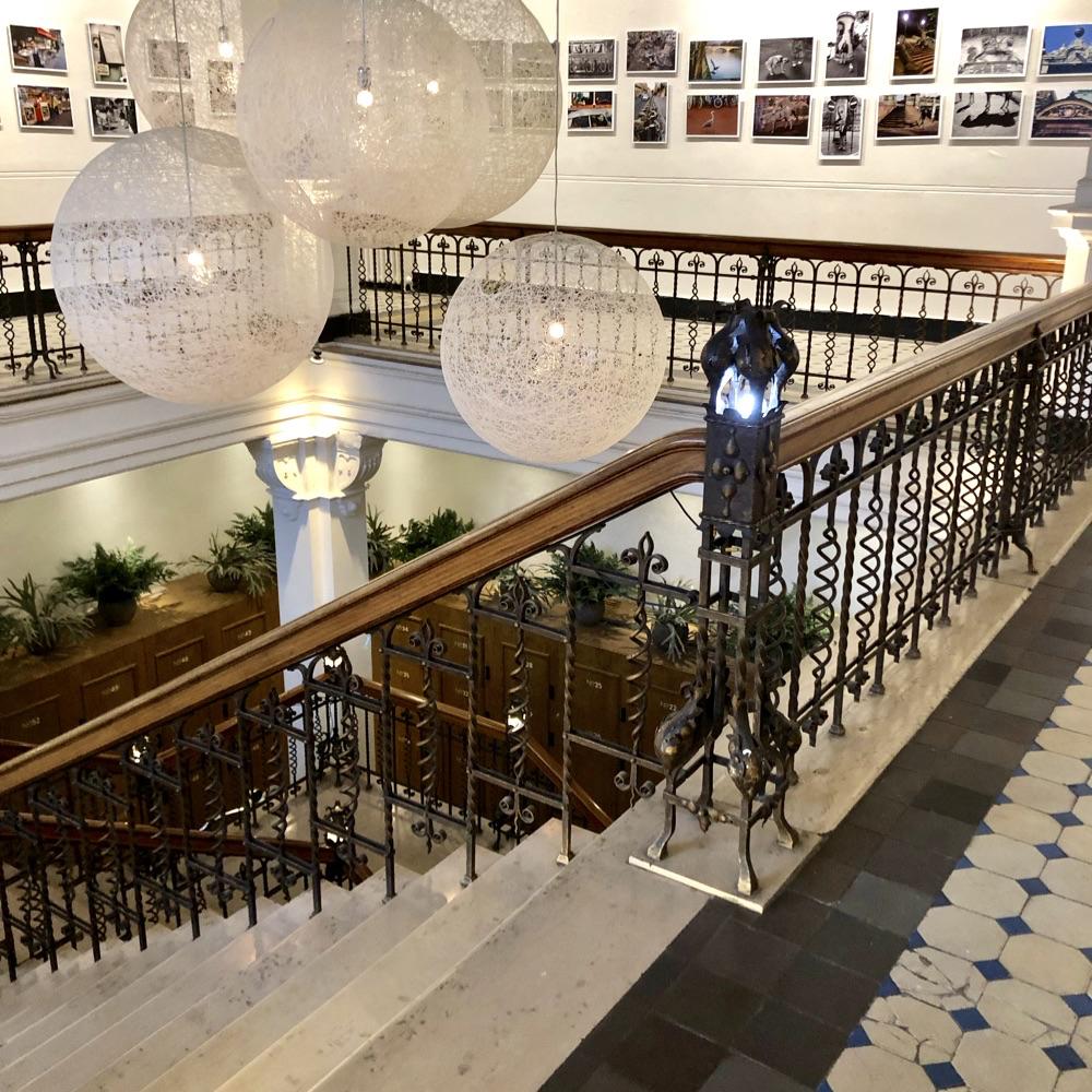 Monumentaal trappenhuis met hout, marmer, zwart witte tegels en moderne lampen